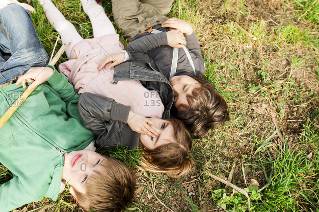Three kids lying in grass