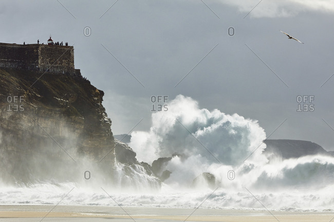 Large waves crashing against a rocky cliff with a lookout on top