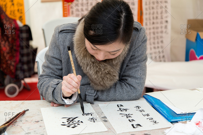 Madrid, Spain - February 21, 2016: Woman writing characters with brush