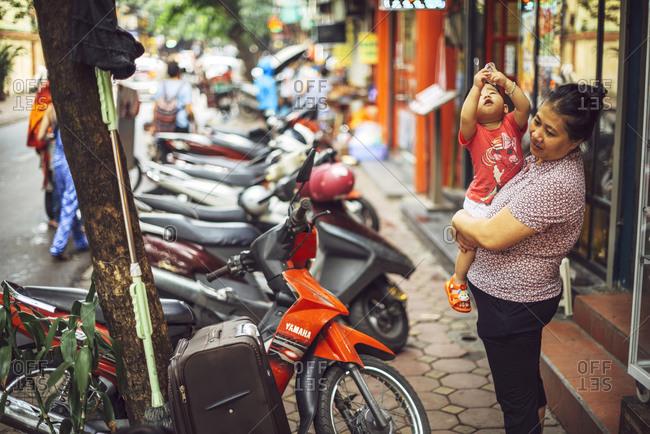 HANOI, VIETNAM - January 10, 2014: Woman holding kid in Hanoi street