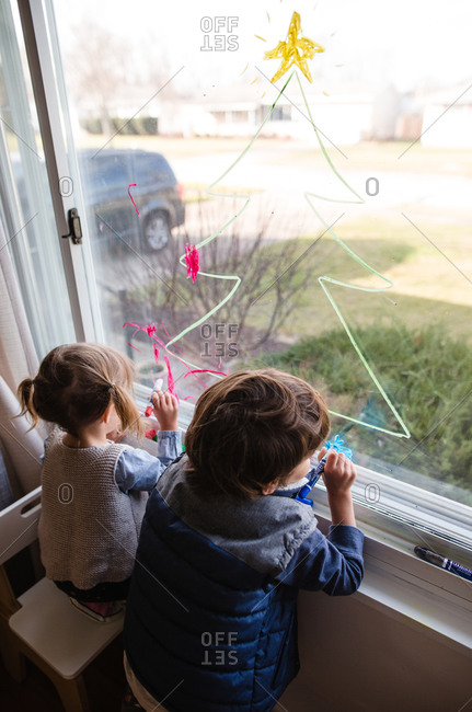 Two young children draw on living room window with glass markers