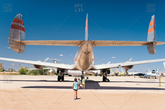 Back view of three children exploring a plane at air show