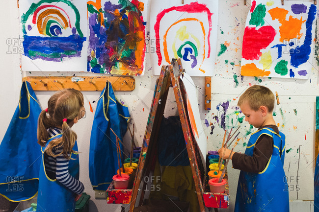 Two preschool kids painting at easels