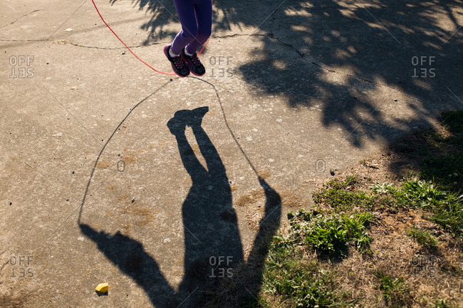 Shadow of child jumping rope on driveway