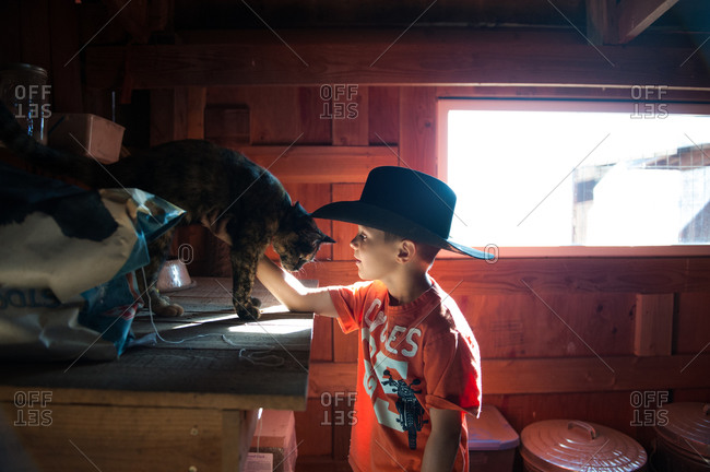 Young boy in cowboy hat petting cat in barn