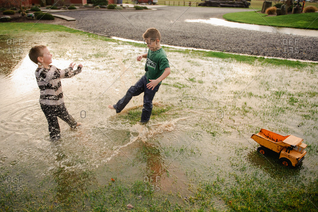 Two young boys play in puddle in flooded front yard