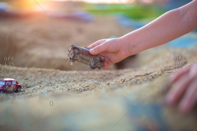 Close-up of a child playing with toy cars in a sandbox