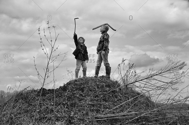 Two boys holding sticks standing on a dirt mound