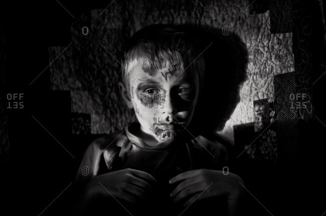 Boy with face painted lying in the shadows