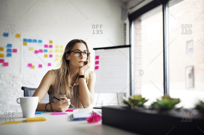 Woman in office lost in thought