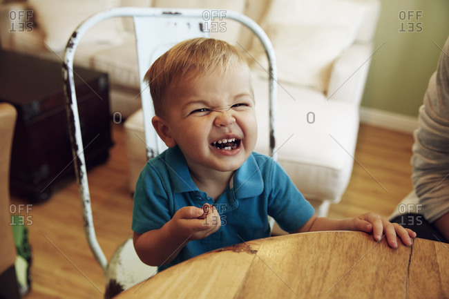 Little boy making a silly face with food in his mouth