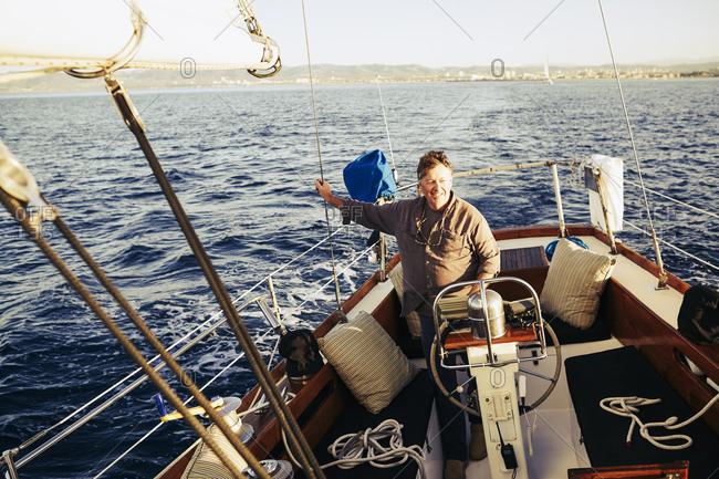 Man standing at the captain's wheel on a sailboat