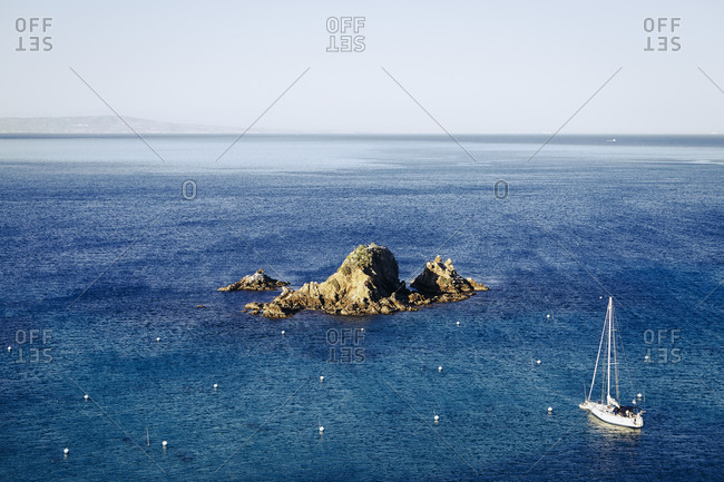 Sailboat in a bay near a rocky island