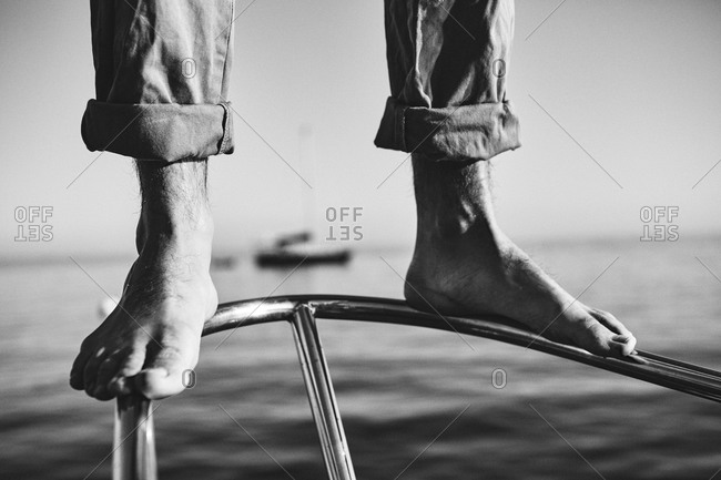 Feet of a man standing on the bow of a sailboat