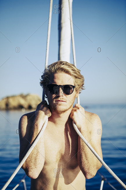 Young man on the bow of a sailboat holding onto ropes