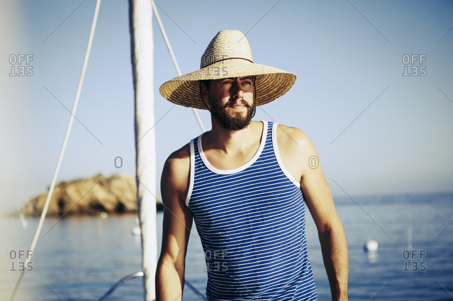 Young man in a straw hat standing on the deck of a sailboat