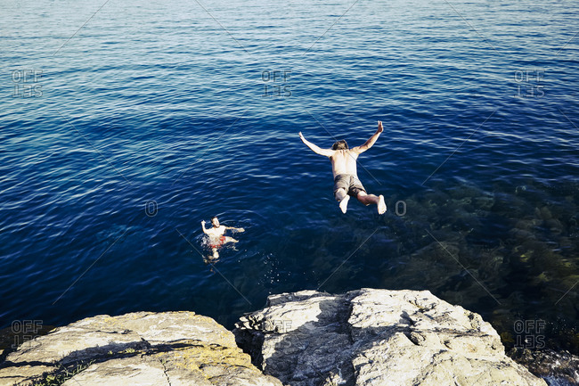 Young man jumping into the ocean to join his friend