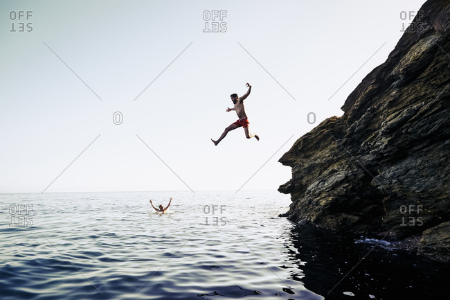 Young man leaping from a rock into the ocean