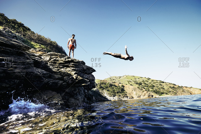 Man diving from a rocky cliff into the sea