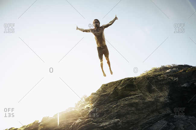 Underside of a man leaping from a rock into the sea