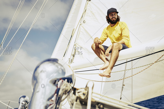 Young man sitting on the mast of a sailboat