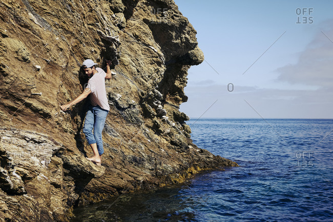 Young man climbing on a seaside cliff