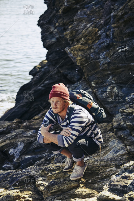 Young man with a backpack crouching on rocks by the ocean