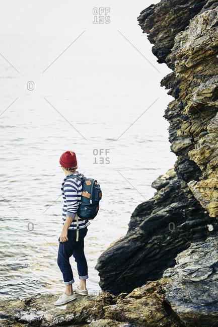 Man standing on rocks overlooking the ocean