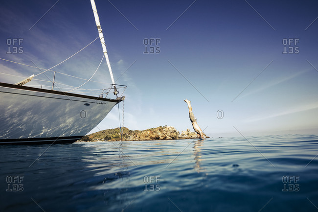 Young man diving from the bow of a sailboat into the ocean