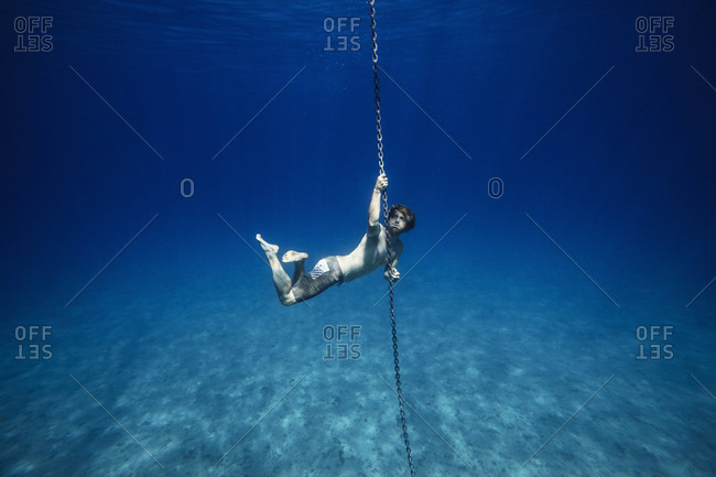 Young man swimming underwater while holding on a boat's anchor chain