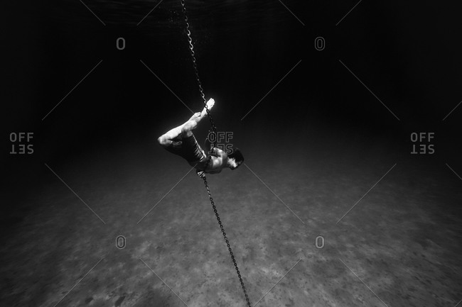 Young man underwater holding onto the anchor chain of a boat
