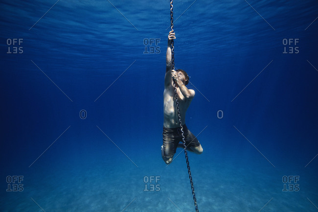 Young man holding onto an anchor chain underwater