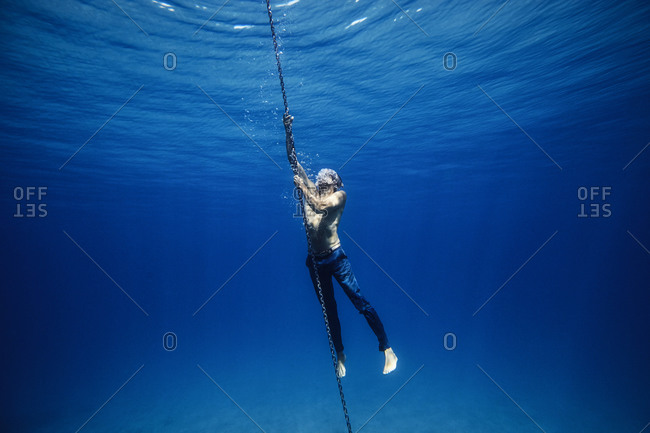 Young man underwater holding onto the chain of an anchor