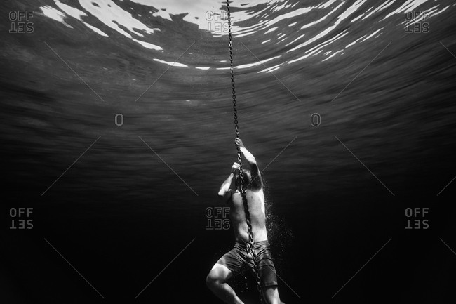Young man holding onto an anchor chain while swimming underwater