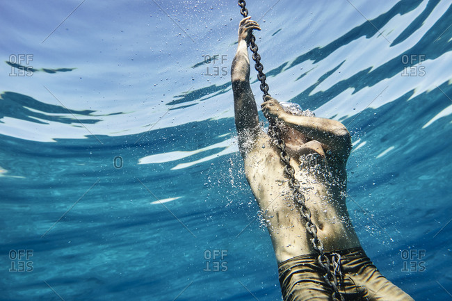 Young man holding onto an anchor chain near the surface of the ocean
