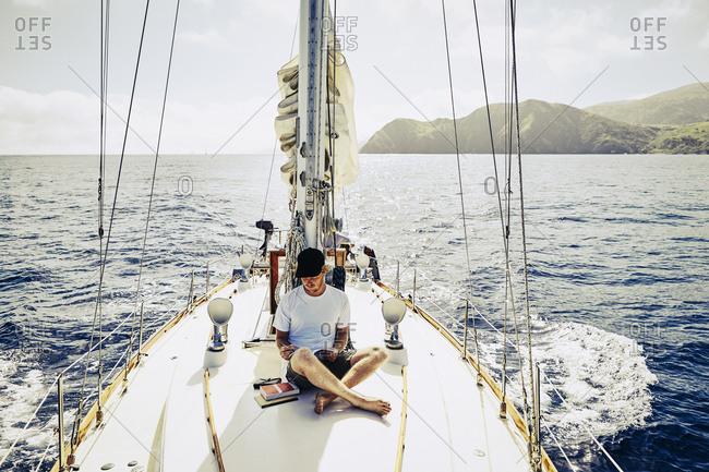 Young man sitting on the deck of a sailboat writing in a journal