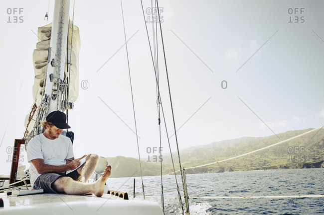 Young man writing in a journal on the deck of a sailboat