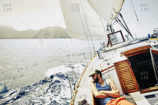 Young man relaxing on the deck of a sailboat