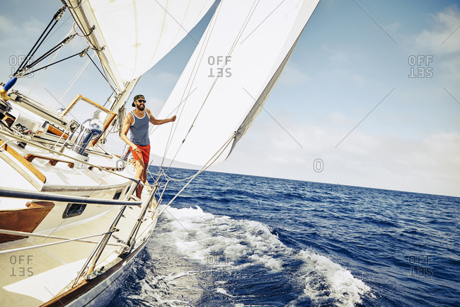 Young man balancing himself on the deck of a sailboat