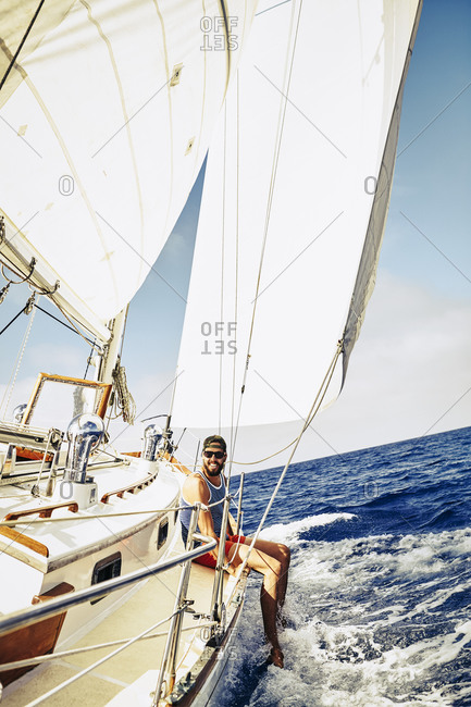 Young man dangling his legs from the side of a sailboat