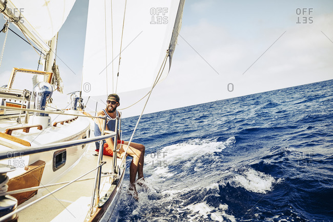 Young man sitting on the side of a sailboat dangling his legs