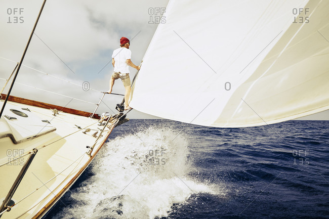 Young man standing on metal bars at the bow of a sailboat