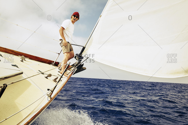 Young man standing on the bow of a sailboat laughing