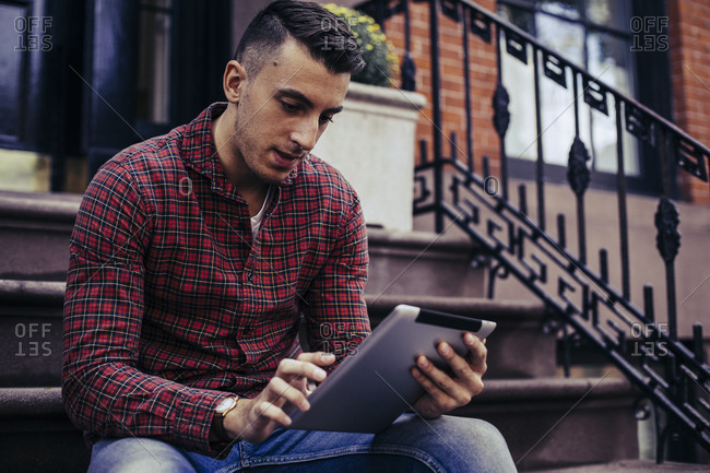 Man sitting on a stoop using a digital tablet