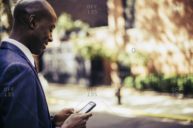 Young African-American businessman standing on a city sidewalk using a smartphone