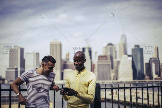 Two men standing together sharing a smartphone with the Manhattan skyline in the background