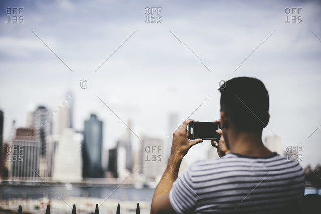 Man taking a photo of the Manhattan skyline with his smartphone