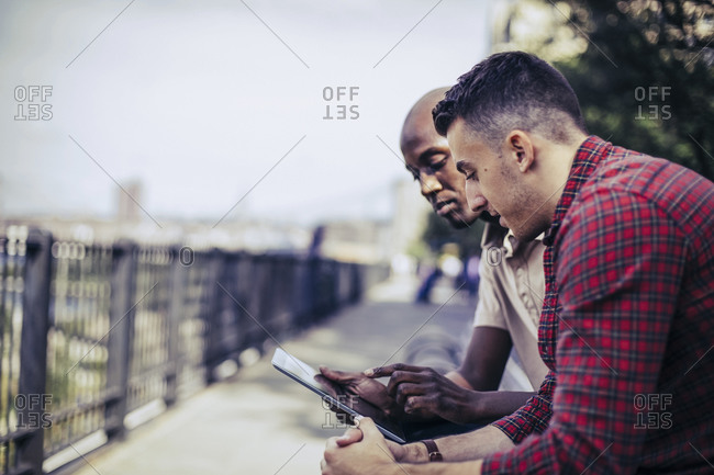 Two men sitting together sharing a digital tablet along the Brooklyn Heights Promenade near New York City