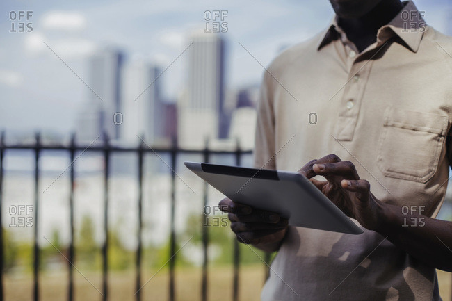 African-American man using a digital tablet with the Manhattan skyline in the background