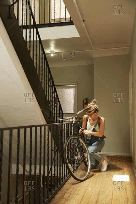 Woman unlocking bicycle parked in an apartment stairway